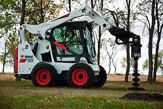 Bobcat skid steer loader picking up dirt