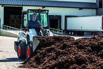 Bobcat small articulated loader picking up dirt