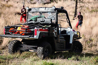 Bobcat utility vehicule with hunters in the background