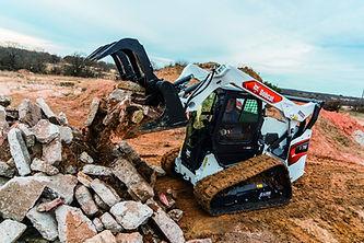 Bobcat track loader picking up rocks
