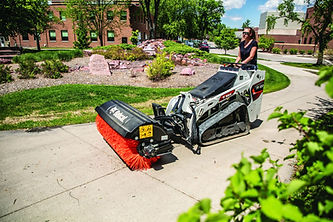 Bobcat mini track loader brushing pavement
