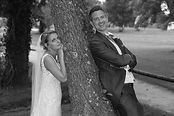 image of bride and groom posing by a tree in black & white