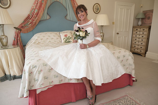 Bride in hotel room poses for photos on a bed before the ceremony