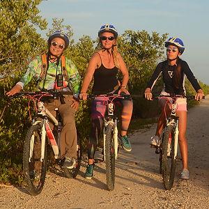 mujeres dando paseo en bicicleta en las orquídeas de sian kaan quintana roo