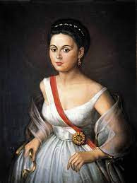 Retrato de una joven Manuela Sáenz con banda roja y un sol en la cintura.