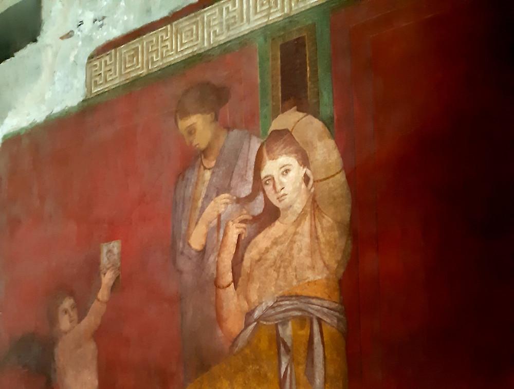 Mural de Pompeya con dos mujeres y un ángel.