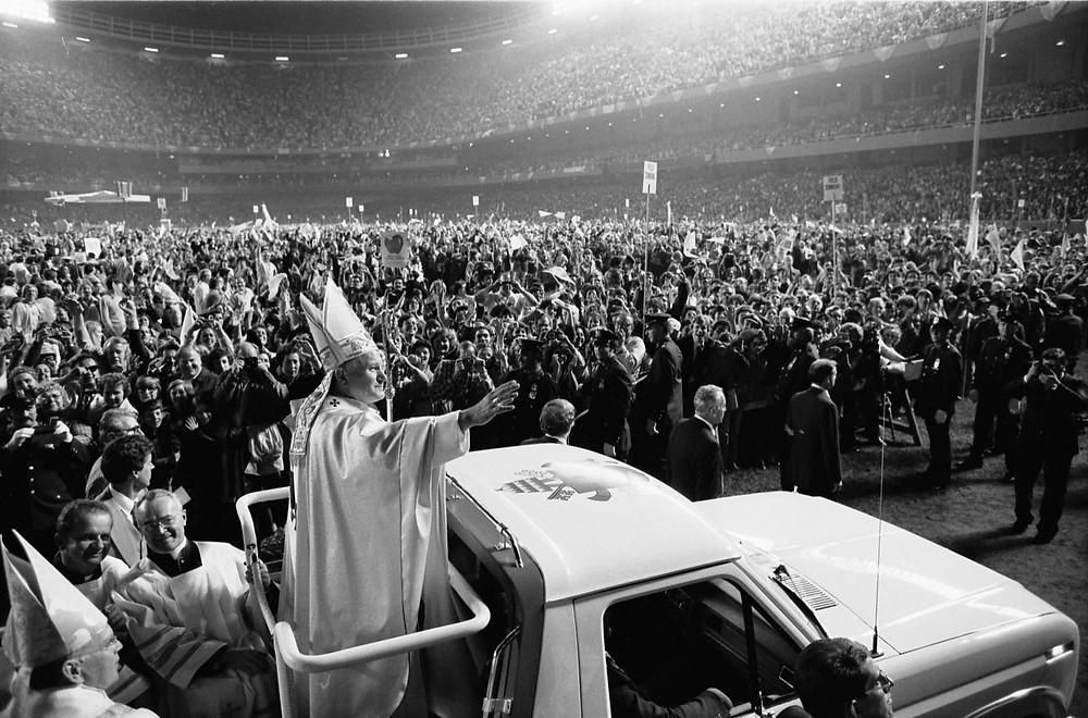 Juan Pablo II saluda a los fieles desde un Papa-móvil.