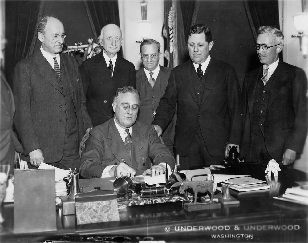 El presidente FDR, sentado, firma un documento mientras unos caballeros le observan.