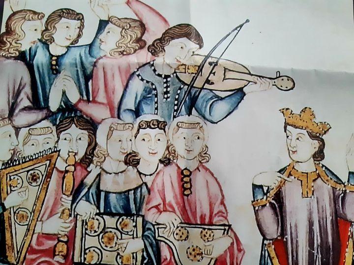 Alfonso X con cortesanos que bailan, tocan instrumentos y juegan.