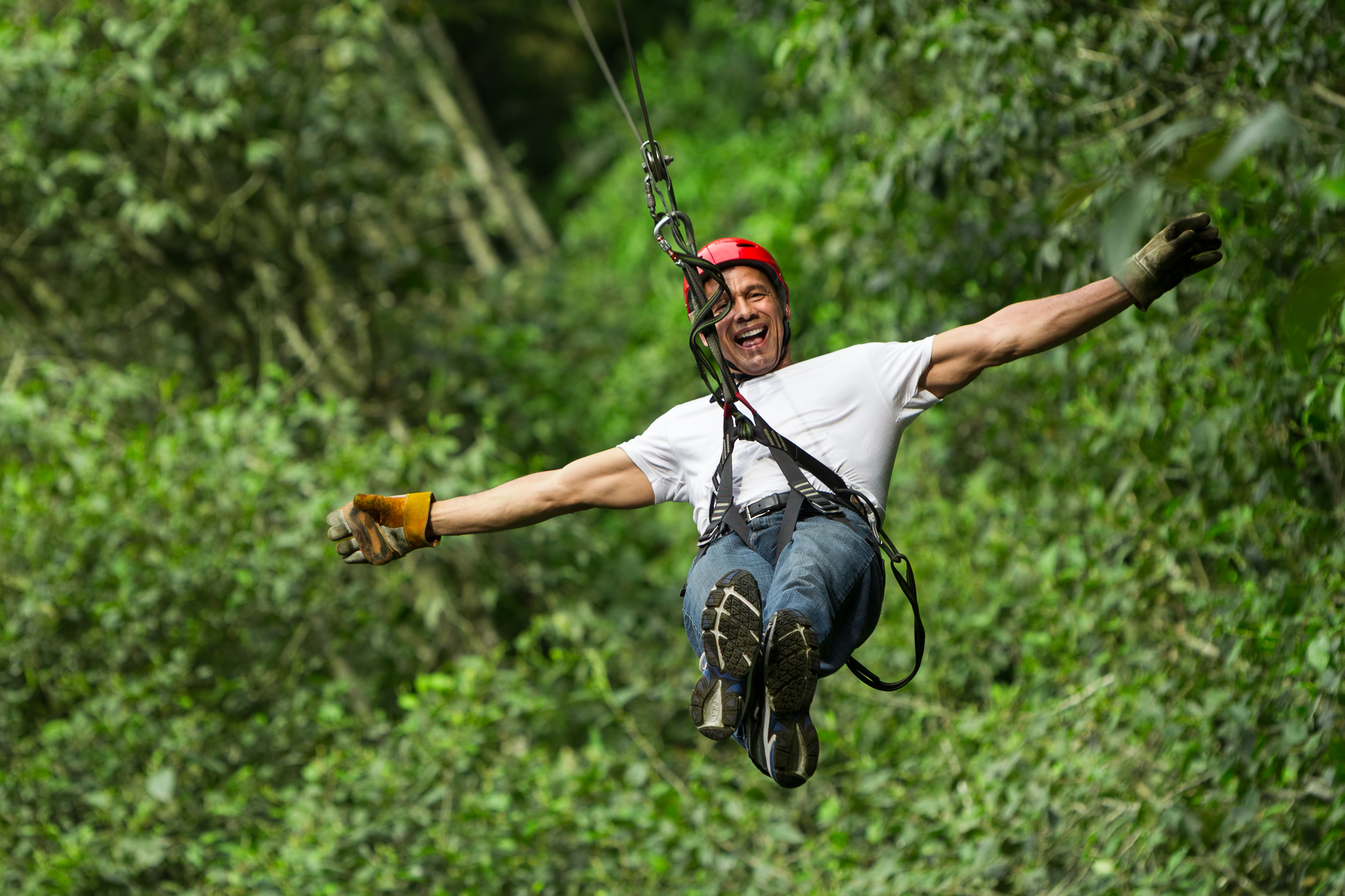 ADULT MAN ON ZIP LINE, ECUADORIAN ANDES_