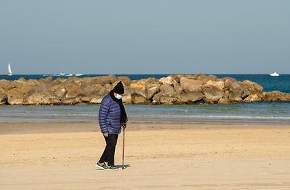 אזרח ותיק עם מקל הליכה צועד בים