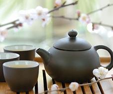 Teillère et 3 tasses noires sur une table, évquant l'asie et la relaxation