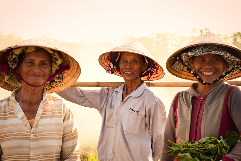 Three Vietnamese female farmers wearing conical hats smiling