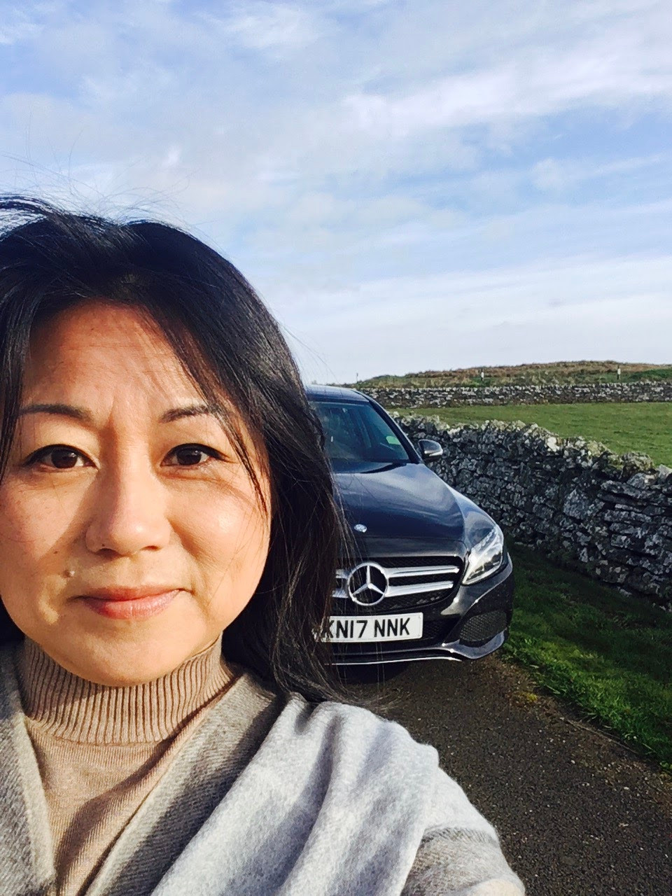 Asian female traveler with Mercedes in Scotland
