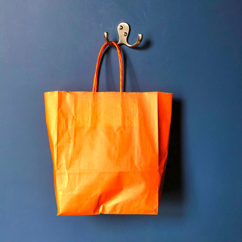 Orange paper bag against slate blue wall