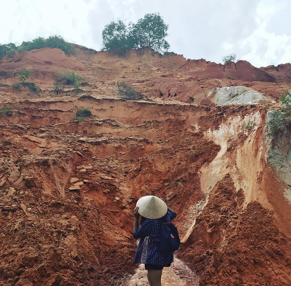 A woman wearing a conical had staring out to the Red clay landscape of Mui Ne, Vietnam