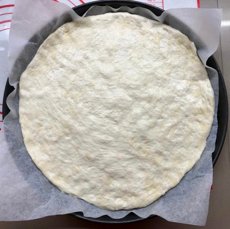 Pizza dough rolled out into pizza pan