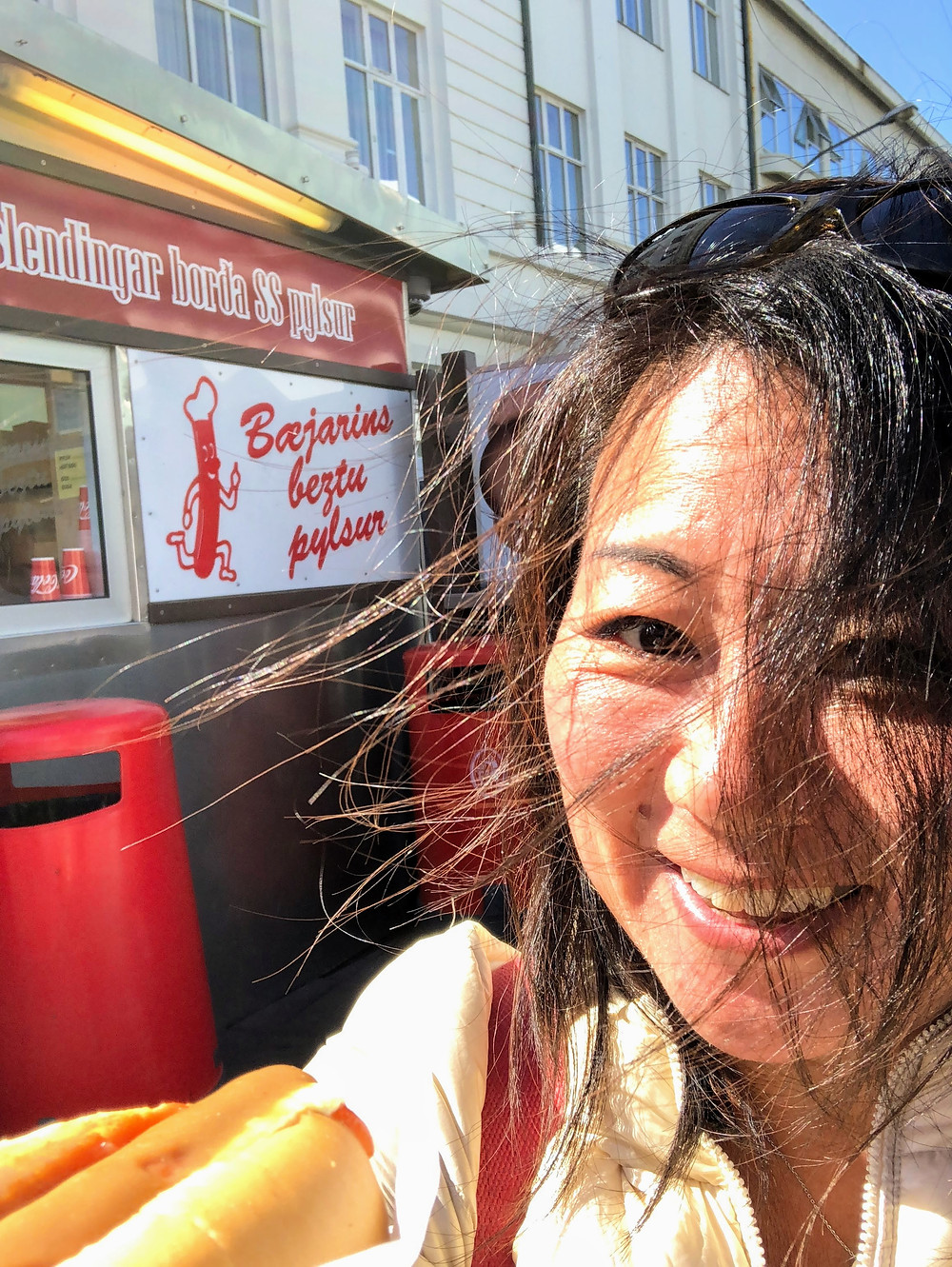 Asian female tourist holding Icelandic hot dog in front of famous stand in Reykjavik