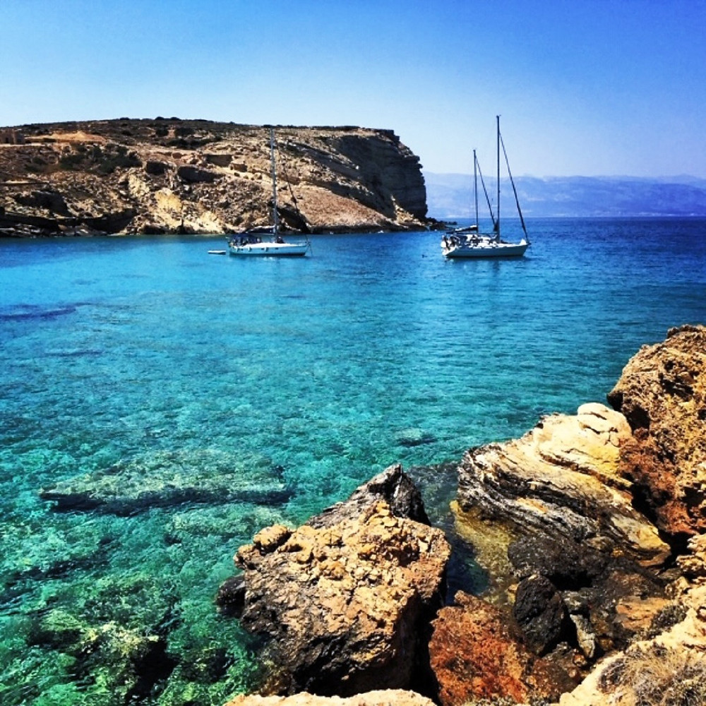 Sailboats on turquoise waters, sunny day on a Greek Isle