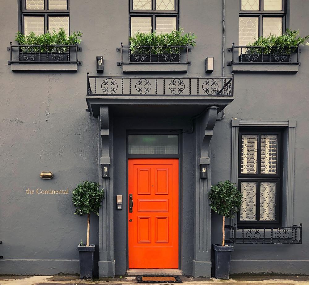 Bright orange door to The Continental Hotel in Galway, Ireland