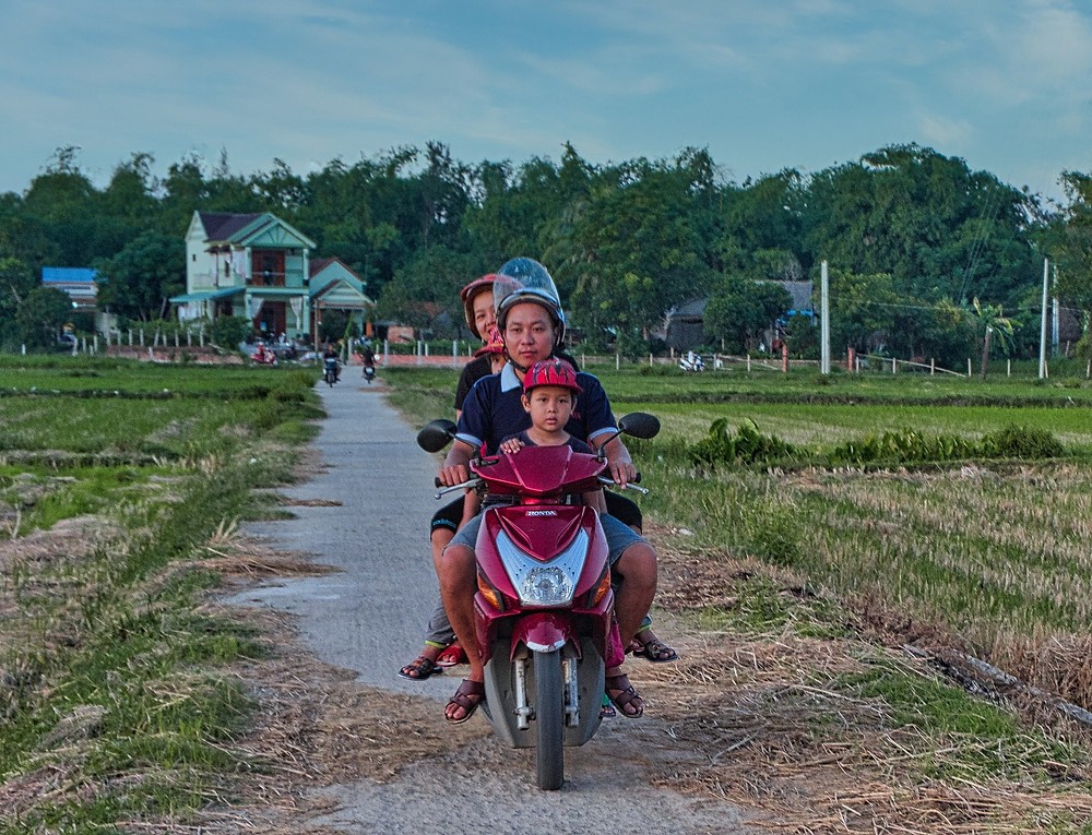 A Vietnamese family of four on one motorbike driving in the countryside