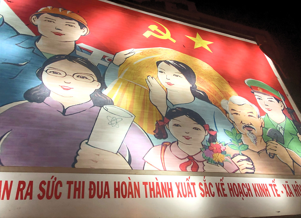Billboard of different types of Vietnamese people in Vietnam with Vietnamese words on the bottom
