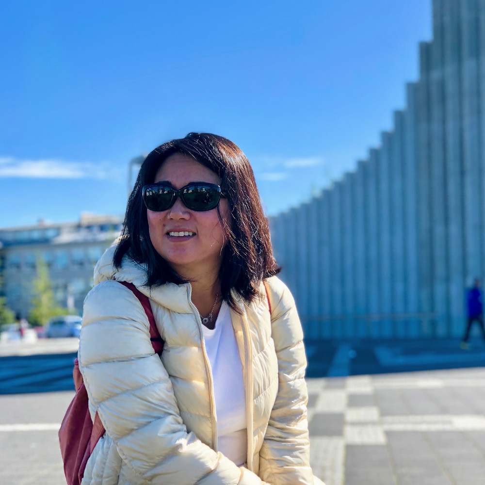 Asian female traveler in front of Hallgrimskirkja in Reykjavik, Iceland
