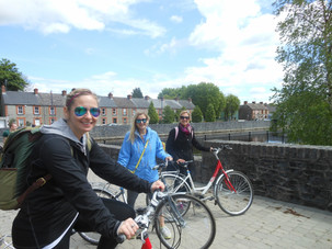 Three women on bicycles wearing sunglasses