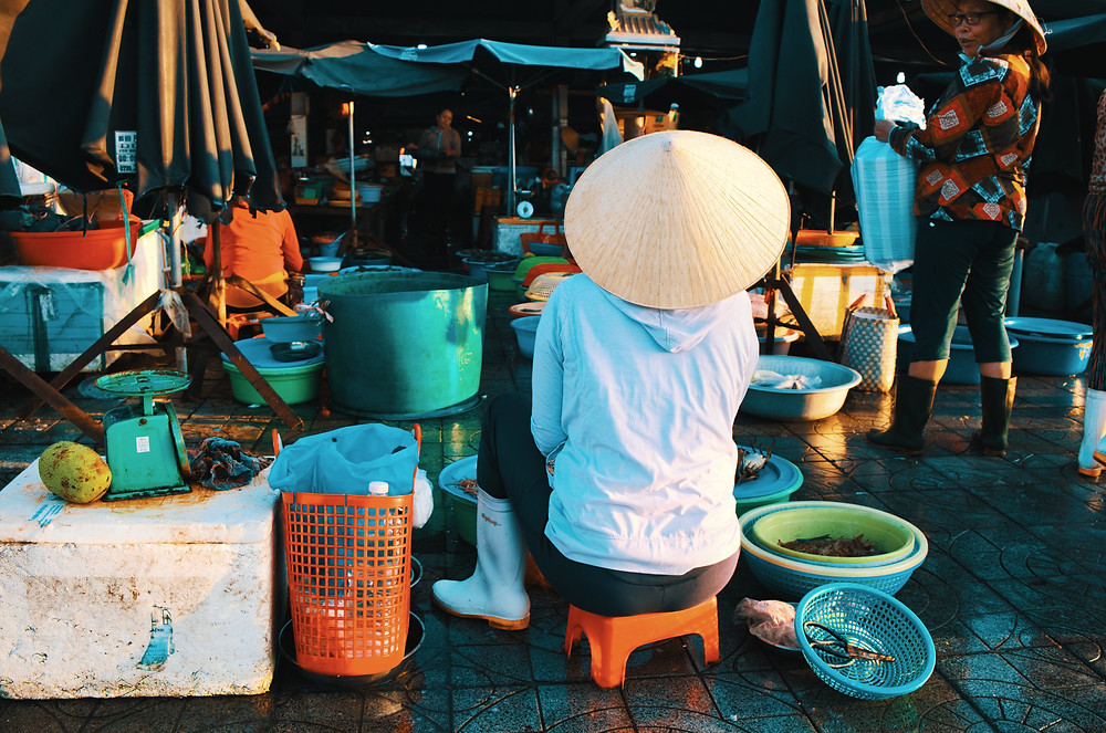Vietnamese woman wearing traditional hat as she works in seafood market in Vietnam
