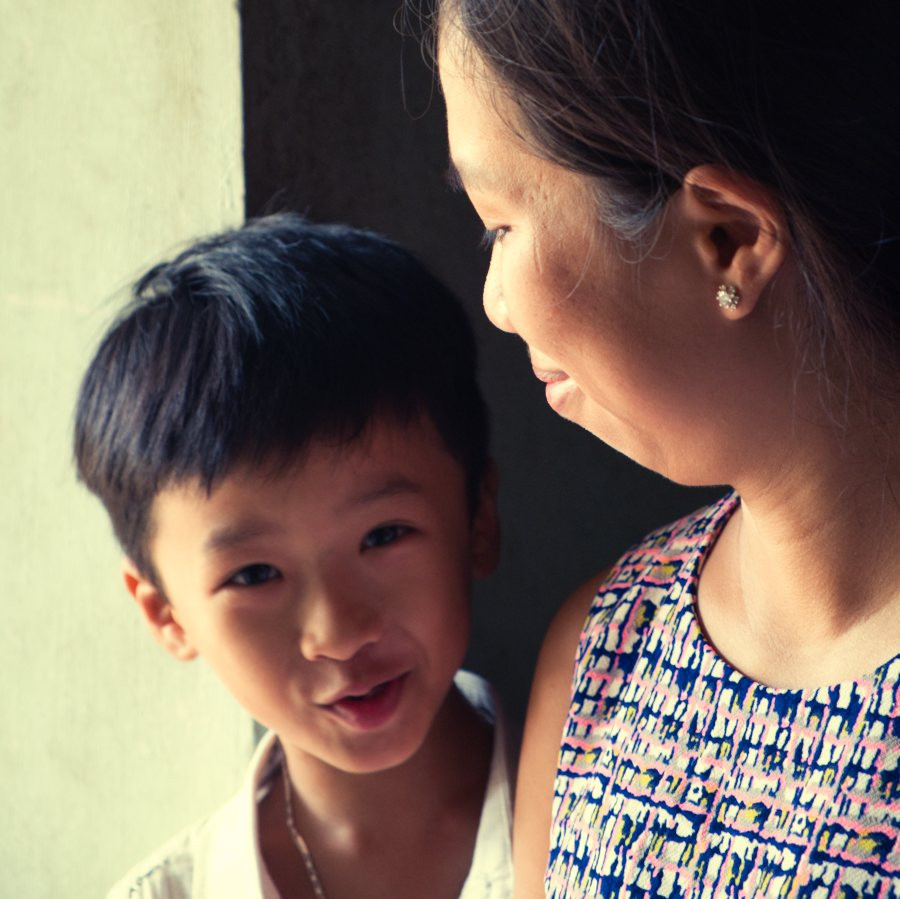 Young Vietnamese boy looking at camera and smirking as a woman looks upon him