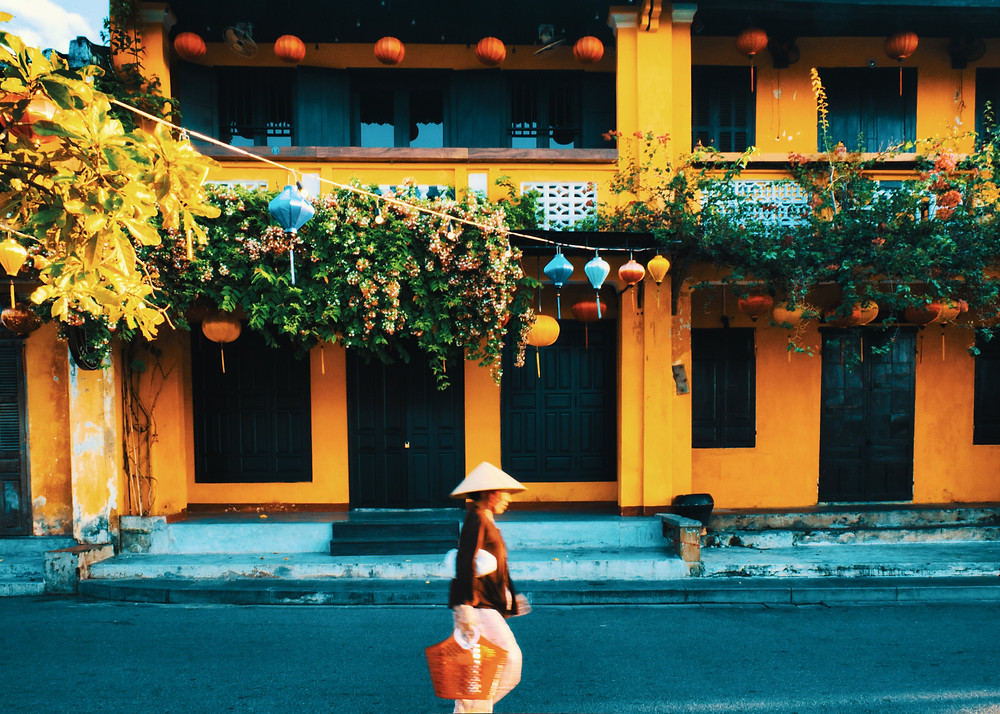 Vietnamese woman wearing a nón lá walking past orange building in Hoi An