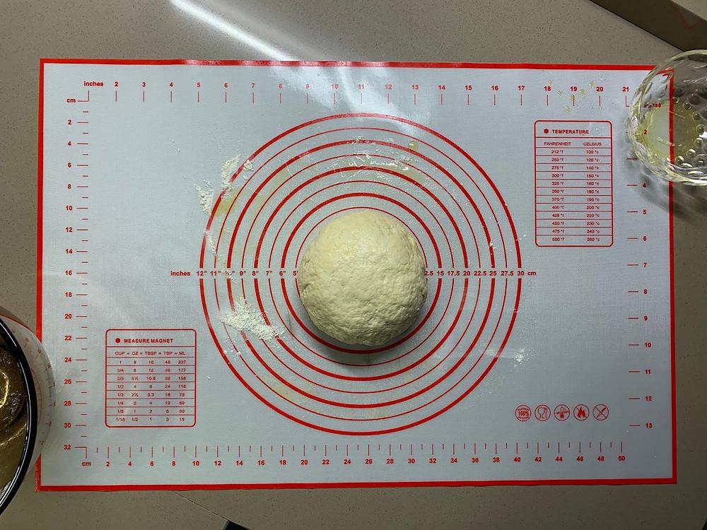 Ball of pizza dough on measuring mat