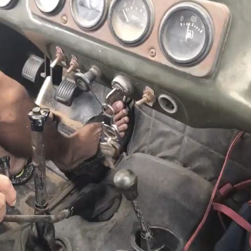 Foot on the pedals of an old Jeep