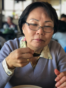 Asian woman wearing glasses savoring a taste of food