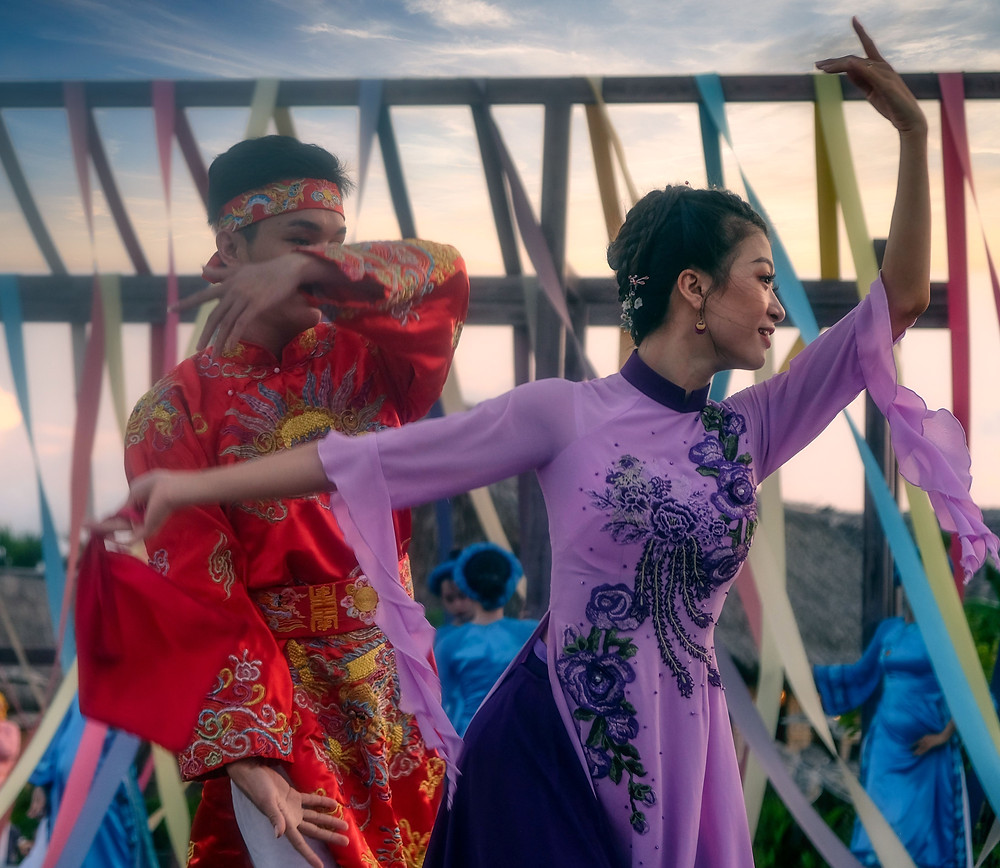 Vietnamese woman and man dancing wearing traditional clothes