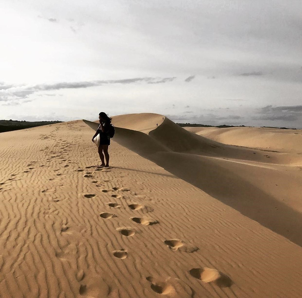 Female solo traveler walking along the White Sand Dunes in Mui Ne, Vietnam