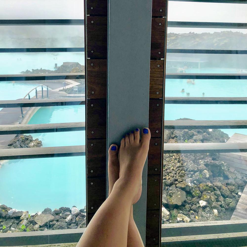 Woman's feet crossed in front of window overlooking the Blue Lagoon in Iceland