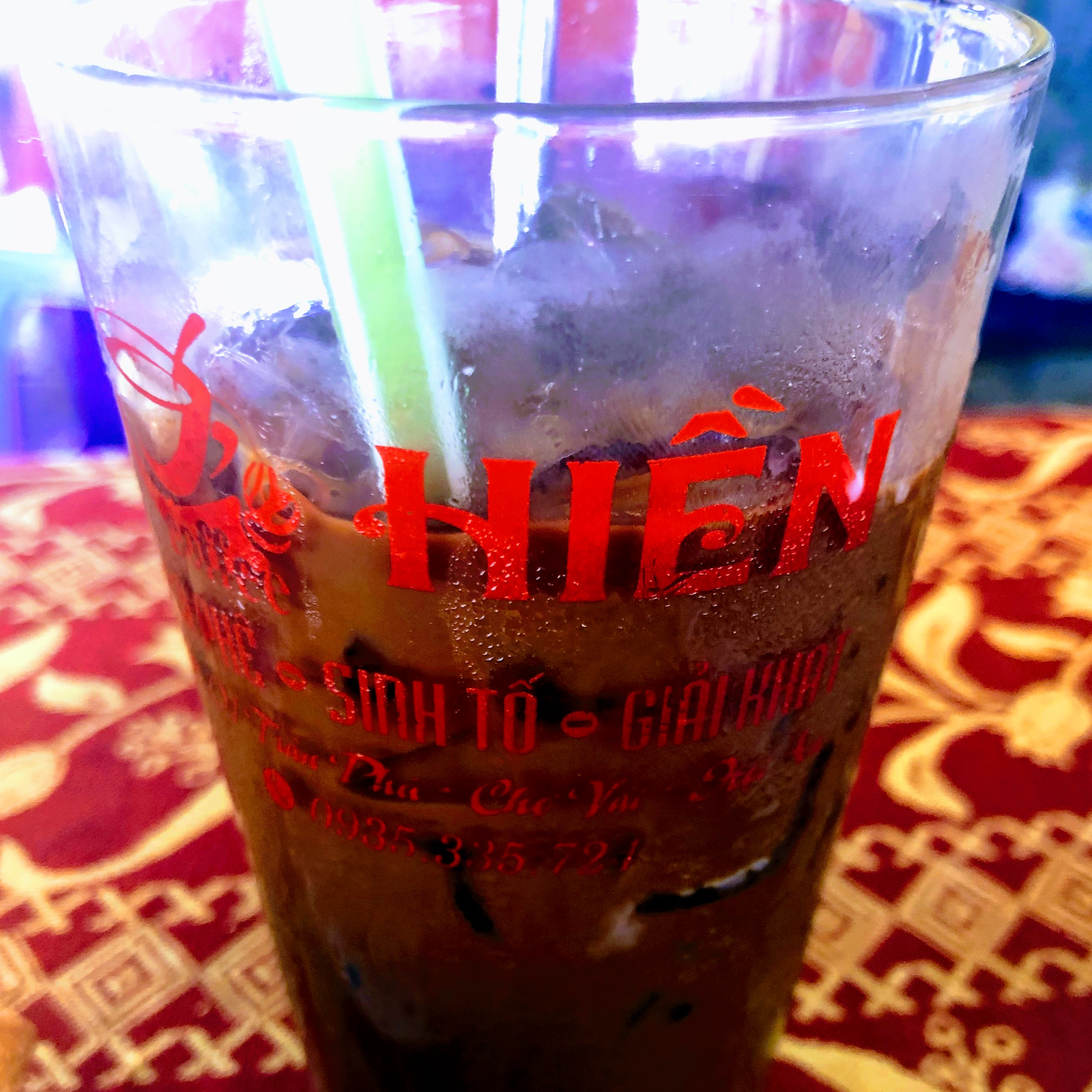 A glass of Vietnamese iced coffee with Vietnamese lettering on the glass