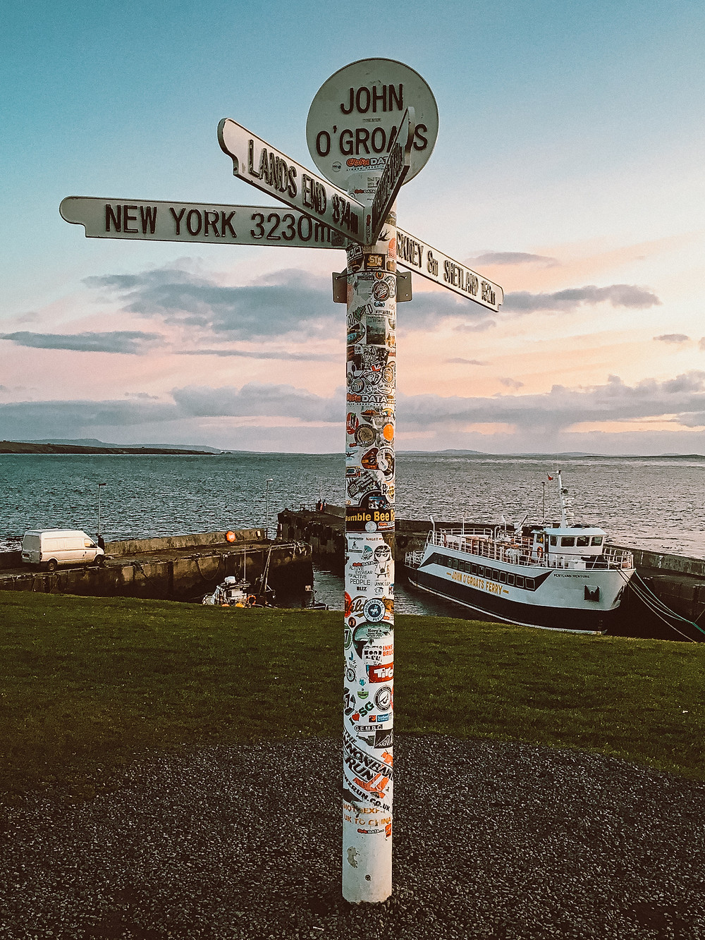 John O'Groats sign post at sunset with boat in background
