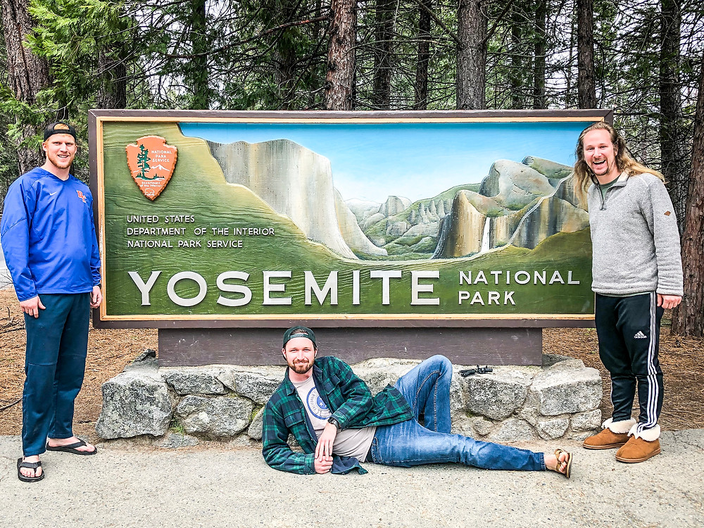 Sam Salerno, Jordan Honer, and Joey Wallberg in front of the Yosemite National Park sign at the entrance to the park
