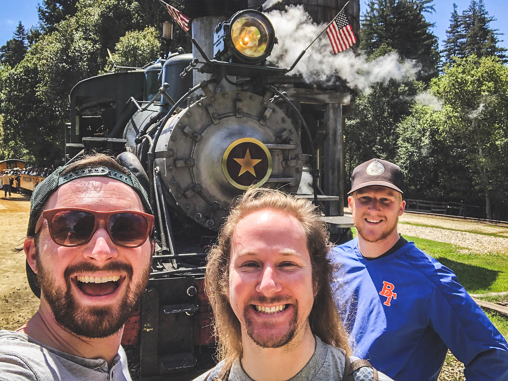 Sam Salerno, Jordan Honer, and Joey Wallberg standing beside a narrow-gauge steam engine at Roaring Camp Railroad in Felton, California