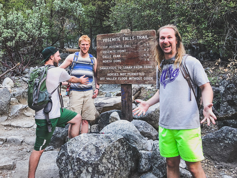 Sam Salerno, Jordan Honer, and Joey Wallberg standing beside the Yosemite Falls Trailhead sign