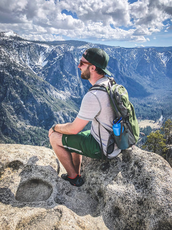 Sam Salerno sitting on the edge of the cliff at the top of Yosemite Falls