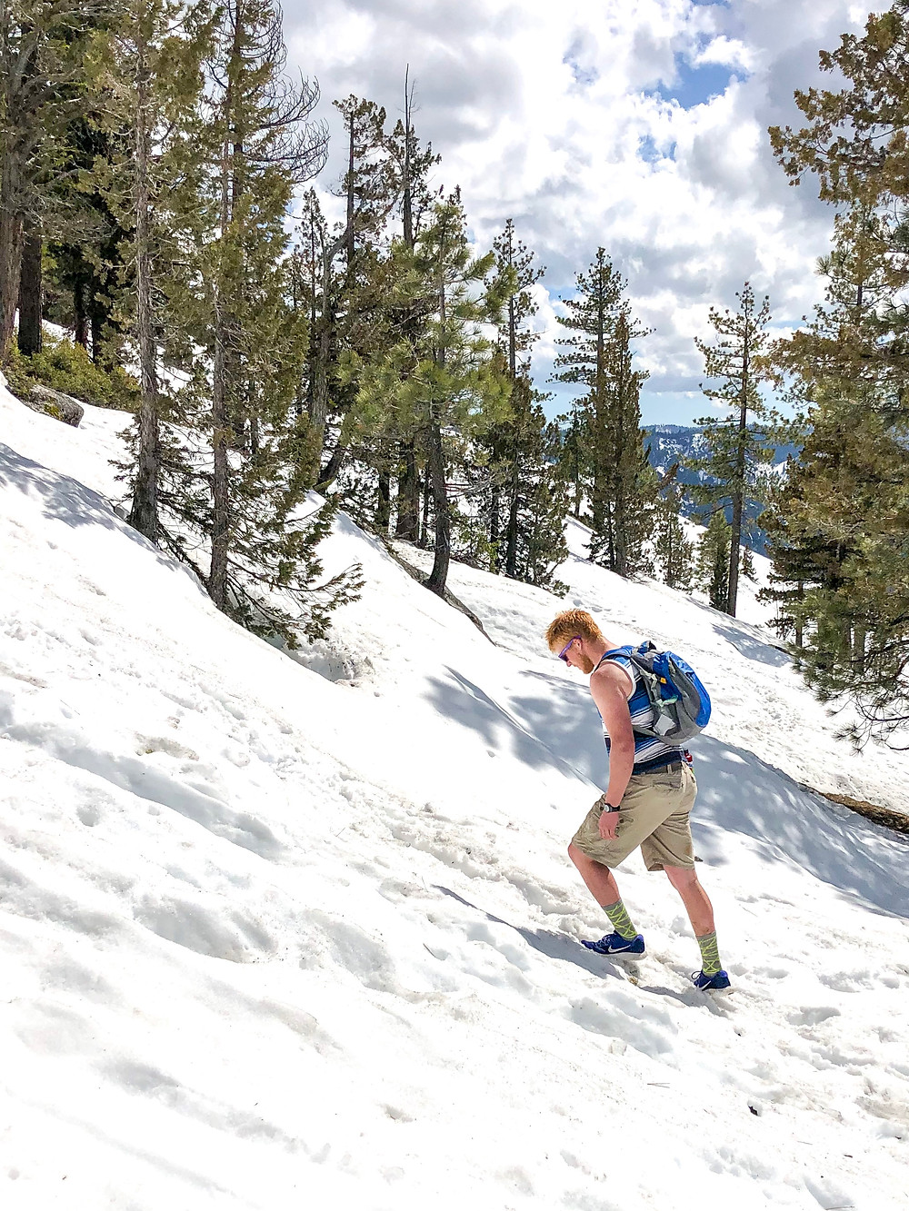 Joey Wallberg hiking up a snowy mountainside in his tennis shoes on the way up to the top of Yosemite Falls