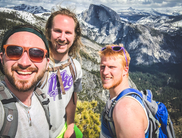 Sam Salerno, Jordan Honer, and Joey Wallberg smiling in front of the view of Half Dome in the distance