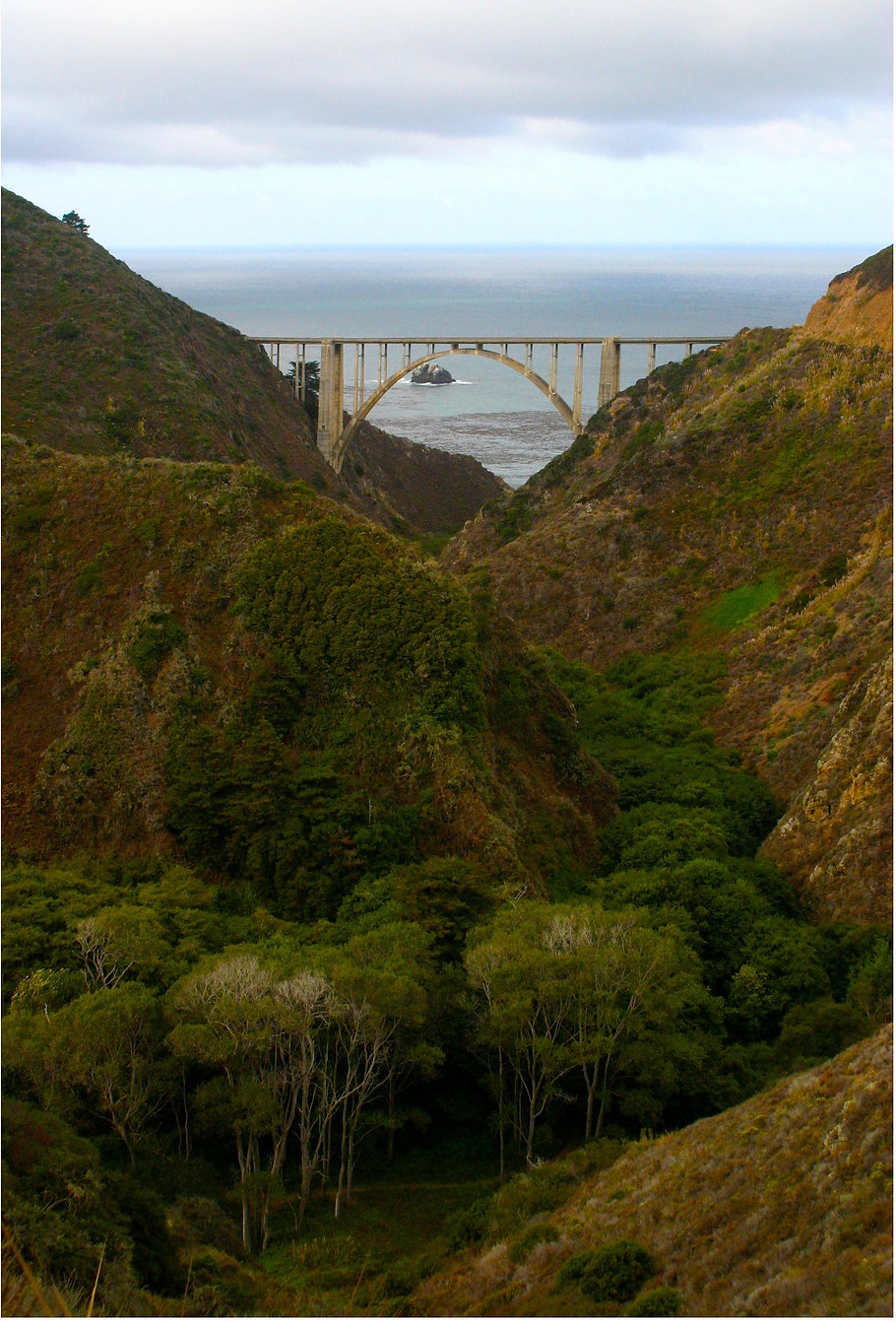 Color photograph by Peter Keresztury of the Bixby Creek  Bridge through the trees. SIgned, titled, matted and framed