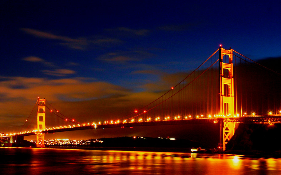 Color photograph by Peter Keresztury of the Golden Gate Bridge lights reflecting on the water. Signed, titled and framed