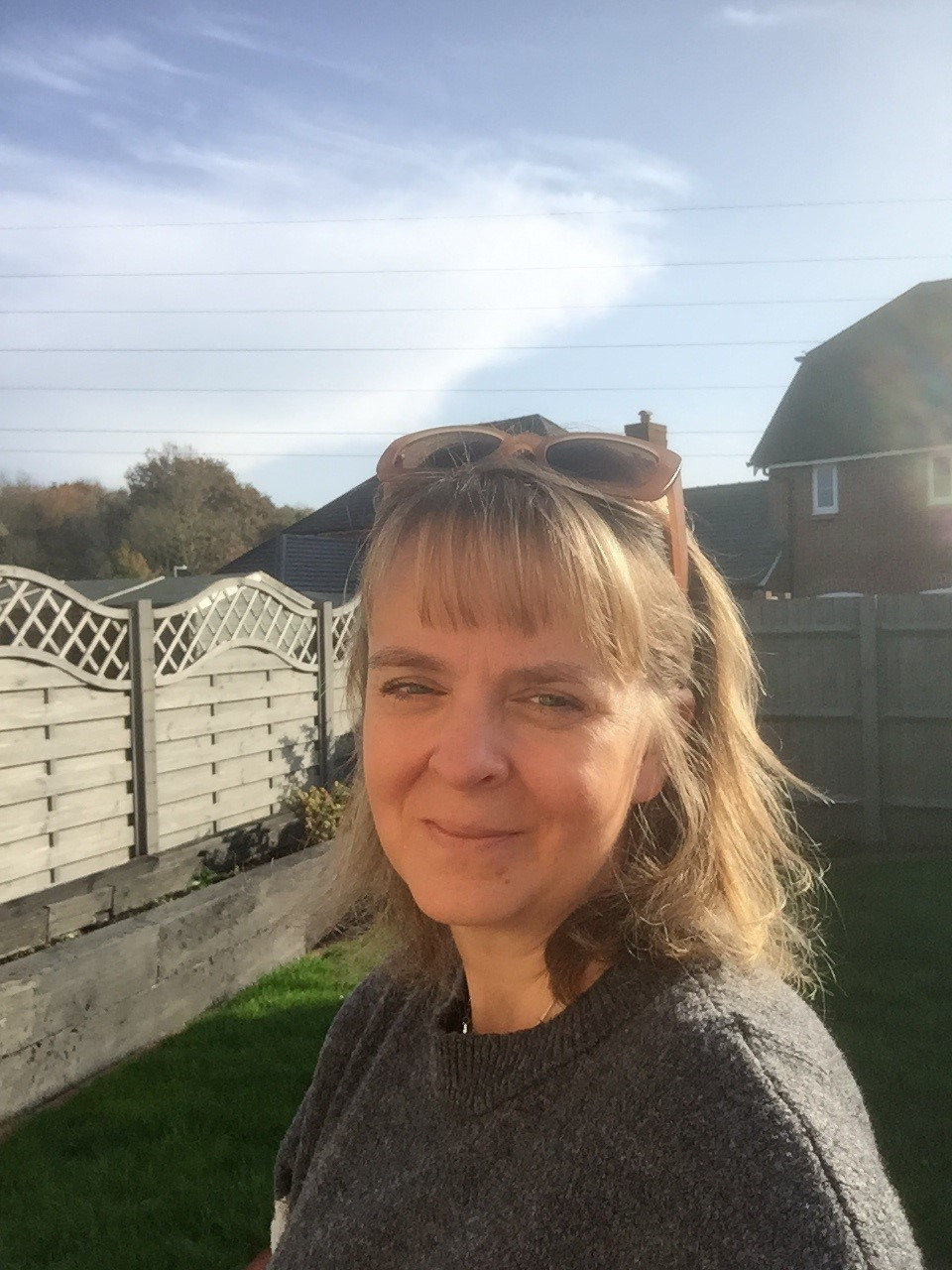 Eddison's teacher Mrs Risley smiling in the garden on a sunny day.