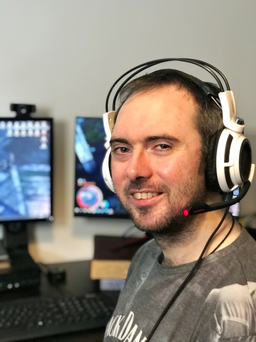 Picture of Ben James smiling at his desk in front of two pc's with his gaming headset on
