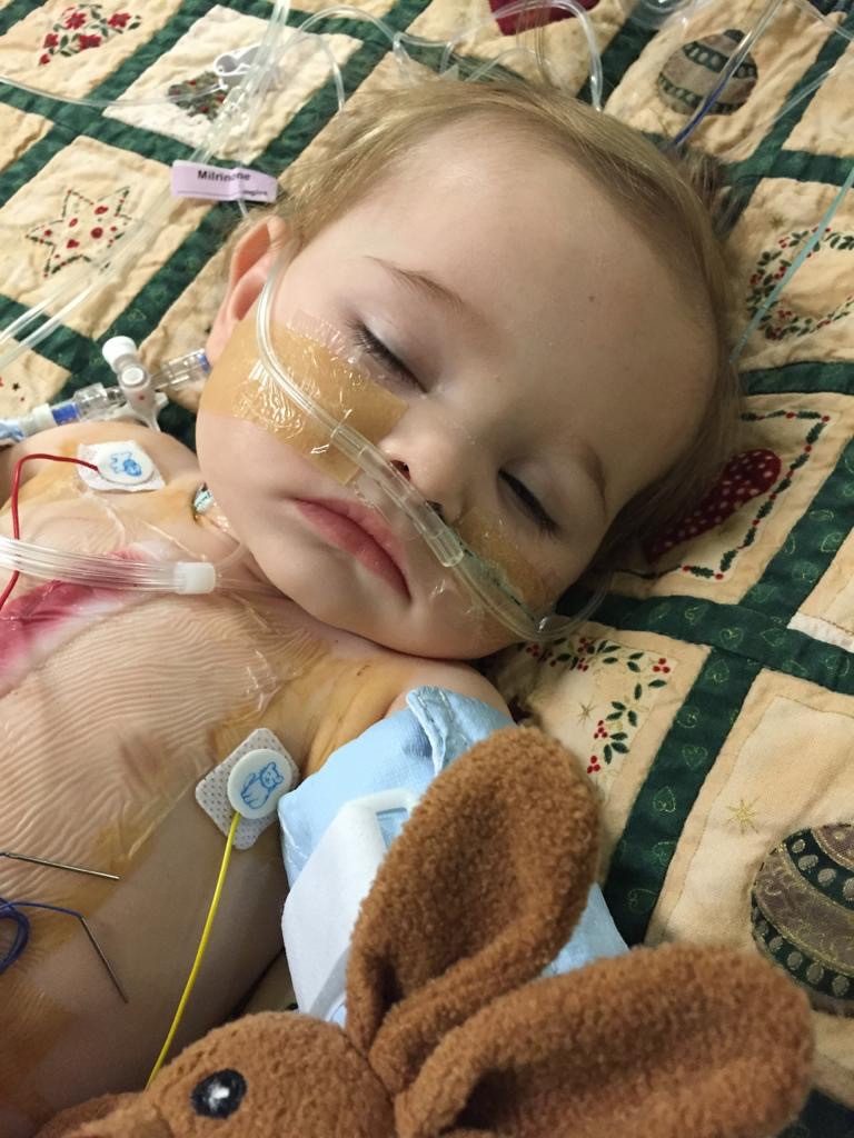 Libby sleeping with various wires and machines connected, fighting for her life